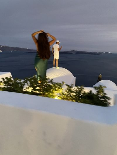 Two overdressed tourists posing on the roof of someone's house in Oia, Sanotirini