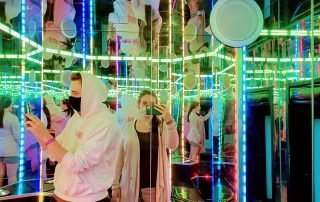 Kristen Cummings and Aaron Owen inside a mirrored room at the House of Eternal Return Meow Wolf Exhibit in Santa Fe, New Mexico during COVID